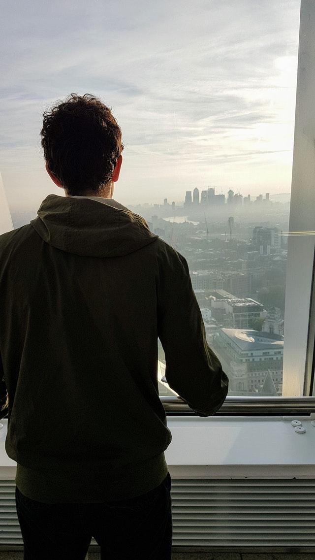 hombre-espalda-ventana-ciudad-atardecer