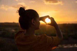 mujer-espalda-sol-corazon-manos